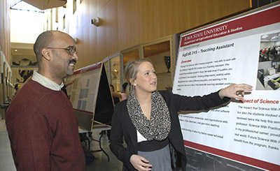 Two scholars discuss a poster presentation